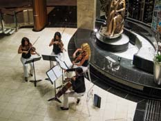 string quartet playing in Crystal Court on ship